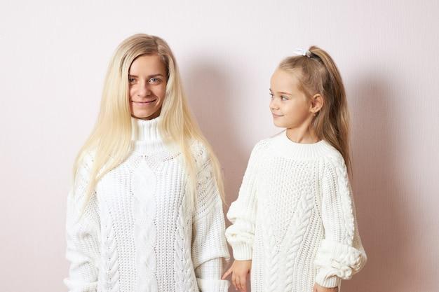 愛、家族、ケア、人間関係の概念。彼女の好奇心旺盛な遊び心のある小さな娘とポーズをとって母性の甘い瞬間を楽しんでいる金髪の長い髪のスタイリッシュな若い女性