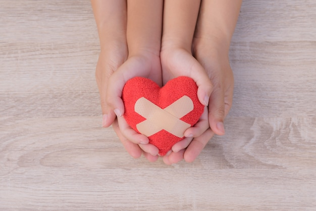 Love, family concept. adult and child hands holding handmade red heart on wooden backgroun