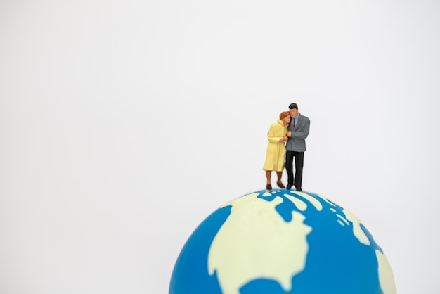 Love and family concept. couple businessman and businesswoman miniature figure people walking and standing on mini world ball