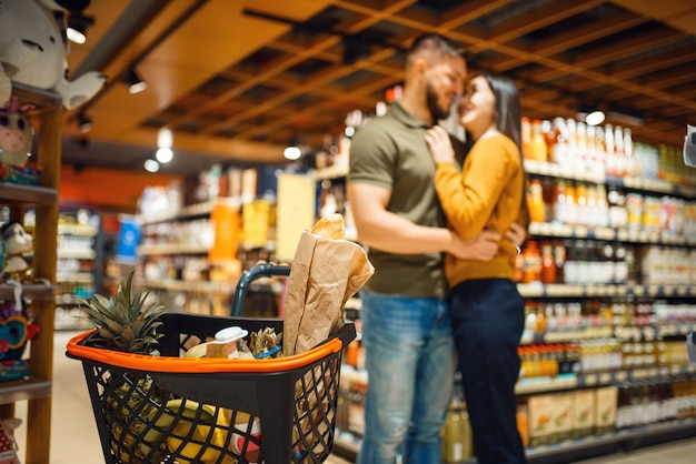 Love family couple hugs in grocery store. man and woman with cart buying beverages and products in market