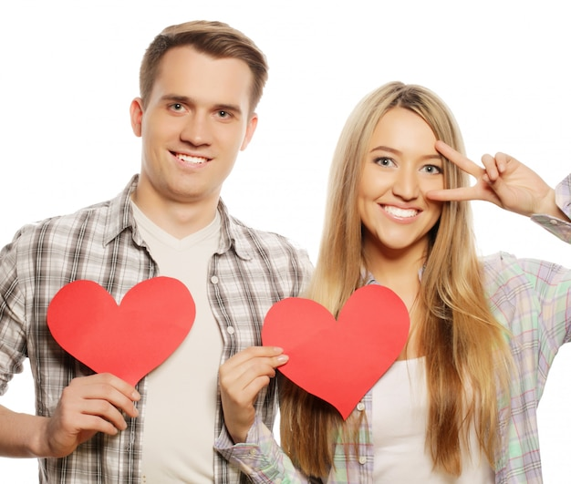 Love, family and people concept: happy couple in love holding red heart