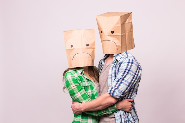 Love, family and relationship problems concept - unhappy couple covering their sad faces with paper bag over white background.