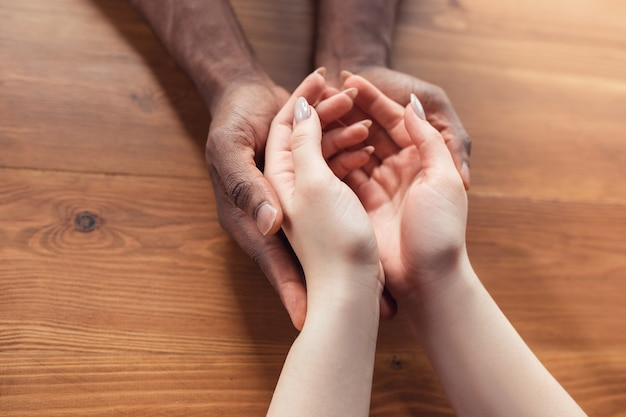 Love, family, support, friendship. close up of african-american male and caucasian female hands holding. concept of relationship, trust and confidence, helping hand, tenderness and warm.