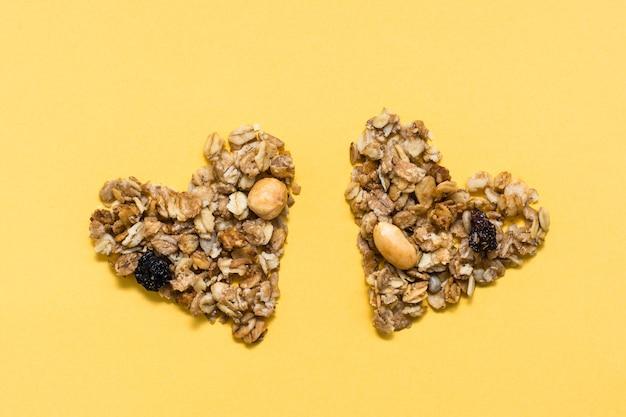 健康食品への愛。黄色の背景に2つのハートの形でオート麦、ナッツ、レーズンから作られたグラノーラ。上面図