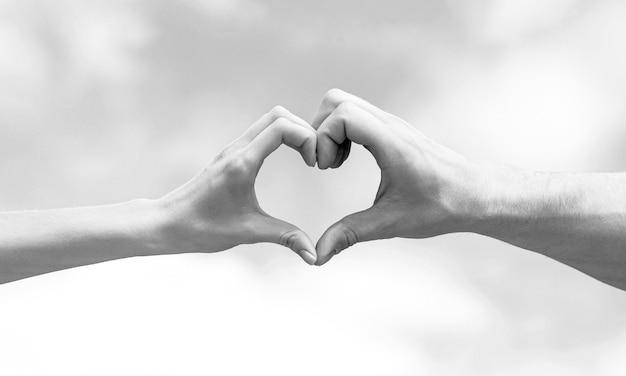 Любовь, концепция дружбы. девушка и мужская рука в форме сердца любят голубое небо. женские и мужские руки в форме сердца на фоне неба. крупный план. черное и белое.