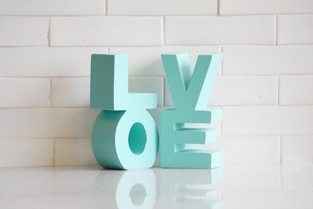 白いレンガの背景を持つテーブルの上の「love」緑のパステルモックアップモデル。