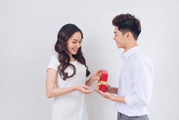 愛。ハンサムな若いベトナム人男性が自宅で美しい女性にプレゼントを与える