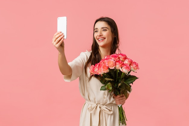 Love, happiness and holidays concept. charming lovely woman in pretty dress, holding flowers and smiling at phone, taking selfie with beautiful bouquet, receive roses for gift, pink wall