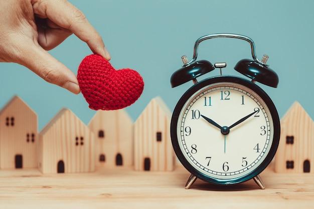 집 개념에 머무를 시간을 위해 나무 집 배경이 있는 시간 시계가 있는 사랑의 마음.
