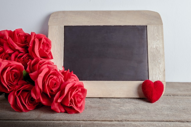 Love hearts shape, red roses and empty chalk board on wood background