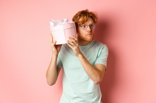 Concetto di amore e vacanze. incuriosito ragazzo dai capelli rossi preme l'orecchio per inscatolare e scuotere il regalo, indovinando cosa c'è dentro, in piedi su sfondo rosa.