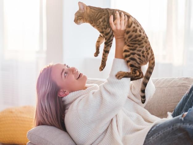 Любите отношения между людьми и животными. пушистый друг. время объятия. девочка держит свою кошечку высоко в воздухе.