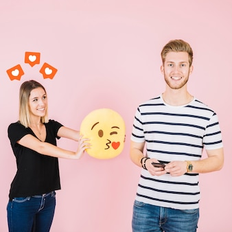 Love icons over happy woman holding kiss emoji near her boyfriend