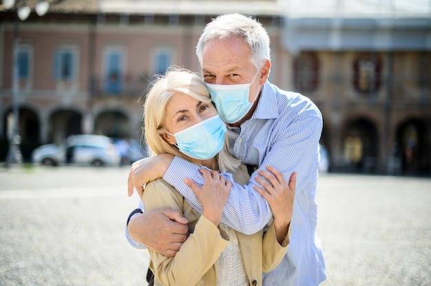 코로나 바이러스 시대의 사랑. 수석 커플 포옹 야외 착용 마스크