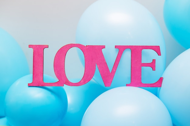 Love inscription and blue balloons
