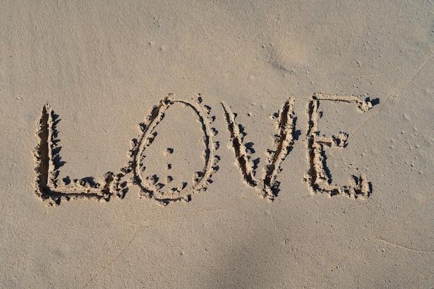 Надпись любви на летнем песчаном пляже. корабль отношений и концепция единения.