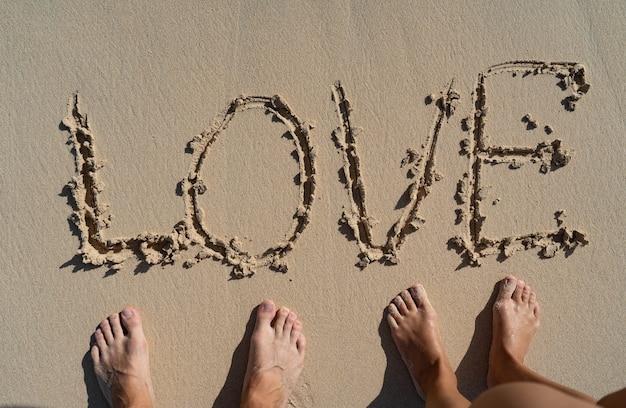 Надпись любовь на летнем песчаном пляже с ногами пары рядом. корабль отношений и концепция единения.
