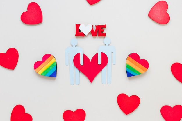 Love inscription with rainbow hearts and gay couple icon