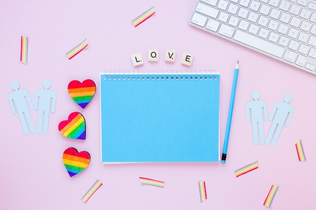 Love inscription with rainbow hearts, gay couples icons and notepad