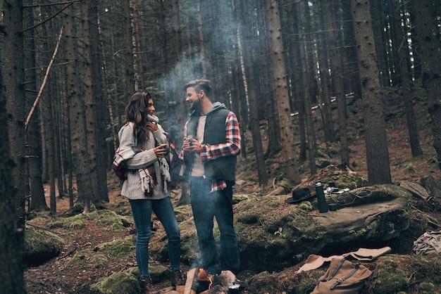 사랑은 그들에게 영감을 줍니다. 모닥불 근처에서 워밍업하는 동안 서로를 바라보며 웃고 있는 아름다운 젊은 부부의 전체 길이