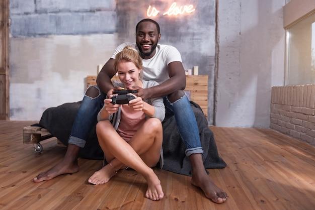 Любовь - это все, что тебе нужно. счастливая пара из разных стран вместе играет в видеоигры, сидя в спальне и улыбаясь.