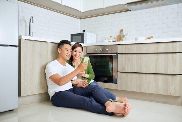Любовь в воздухе. красивая молодая пара пьет кофе и апельсиновый сок, сидя на полу кухни дома
