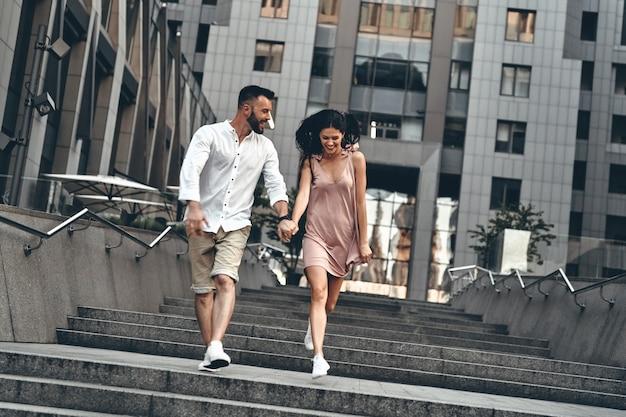 사랑은 공중에 있습니다. 야외에서 계단을 내려가면서 손을 잡고 웃고 있는 아름다운 젊은 부부