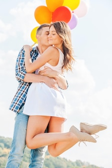 사랑은 공중에 있습니다. 그녀에게 키스하는 동안 아름다운 젊은 여자와 풍선을 들고 남자