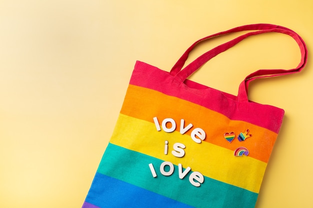 Love is love text rainbow reusable bag against yellow background
