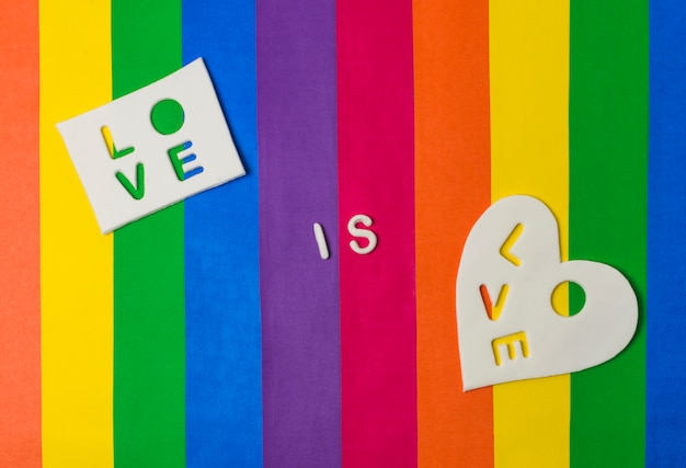 Love is love words on tablets on bright lgbt flag