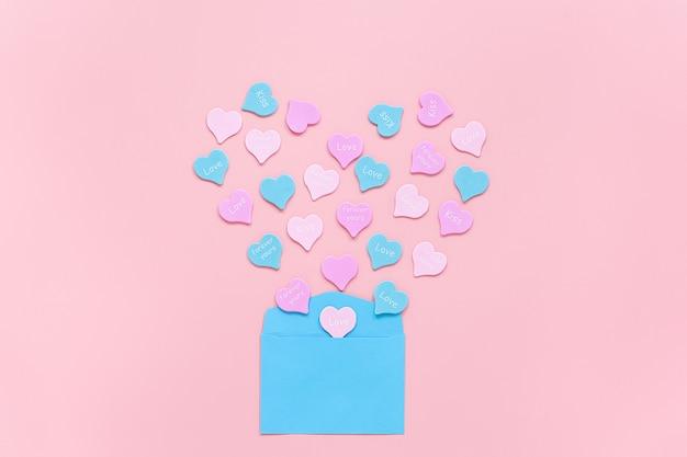 Разноцветные сердечки с надписью love, kiss, forever yours разлетаются в форме сердца из синего бумажного конверта на розовом