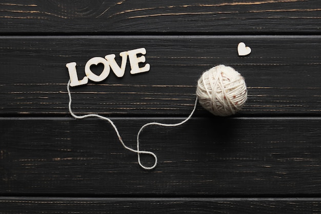 Love for knitting, a tangle threads and the inscription love on dark surface