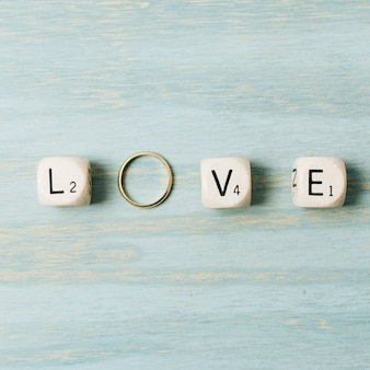 Love letter cubes with wedding golden ring on wooden texture backdrop