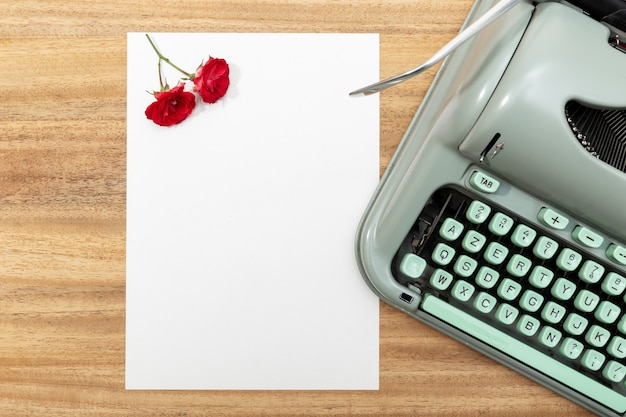 Love letter. desk with blank paper, retro typewriter and red roses and petals