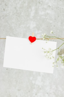 The love letter hangs on rope and a flower on a light background.