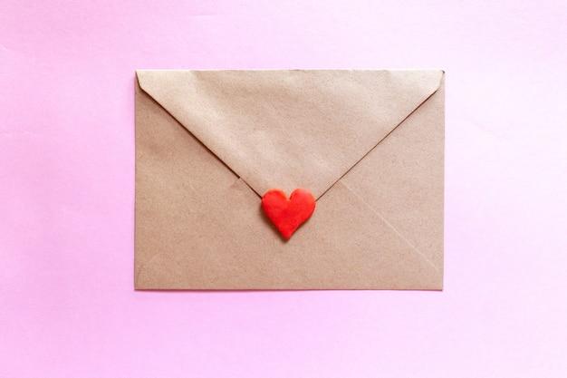 ピンクの背景に粘土の赤いハートとクラフト封筒のラブレター。