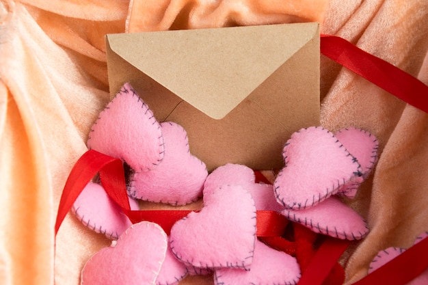 Love letter or invitation in envelope from old paper with pink hearts decorated with red ribbon.