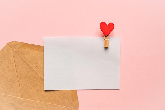 Макет любовного письма. открытка с булавкой и красным сердцем