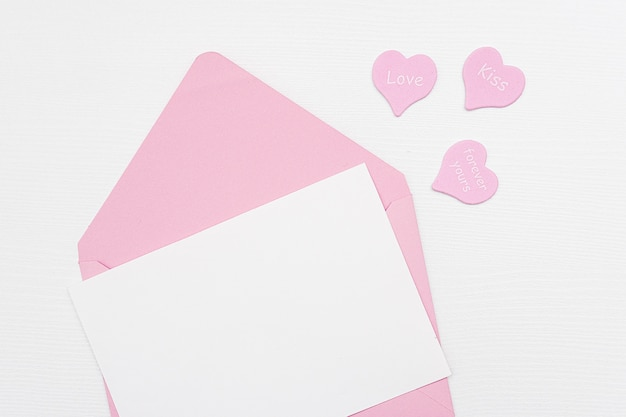 Love letter. pink envelope with white blank card and hearts on white background. top view flat lay mockup for your text.