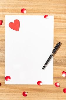 ラブレター。白いカード、赤いハート、木製テーブルの上のペン。平干し。上面図。