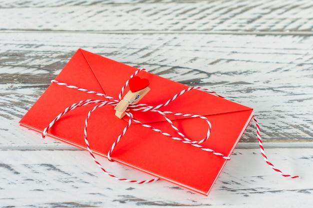 木製の背景に紙のハートとラブレター。聖バレンタインデーのお祝いグリーティングカード。