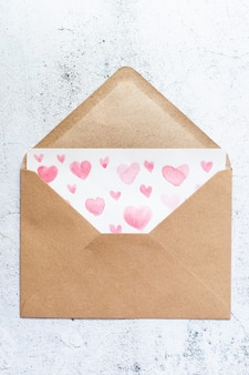 Love letter with water color pink hearts in a craft envelope on white wood background.