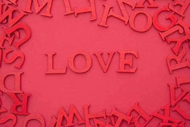 Love lettering, 3d wooden red letters on red background. creative valentine's day