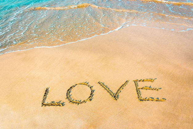 Love lettering on the beach with wave