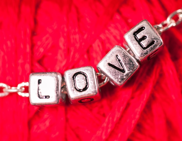 Love letters on the chain close up on red background