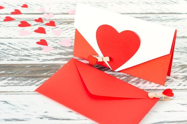木製の背景に紙のハートのラブレター。聖バレンタインデーのお祝いグリーティングカード。