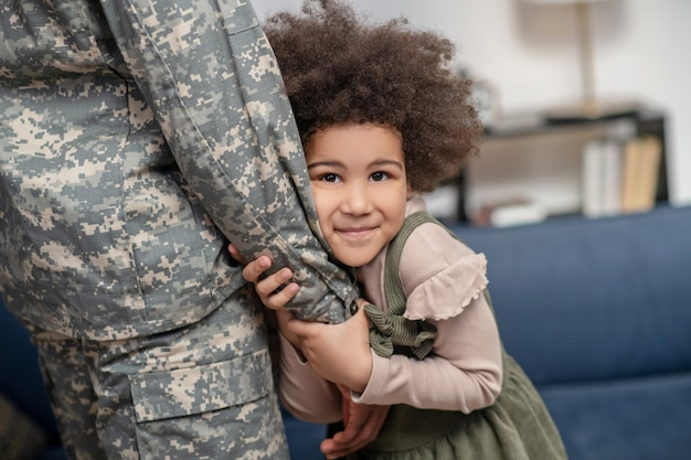 Love. little curly cute african american girl hugging dads hand in military uniform standing smiling dreamily