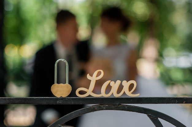 Love lock and newlyweds on background.