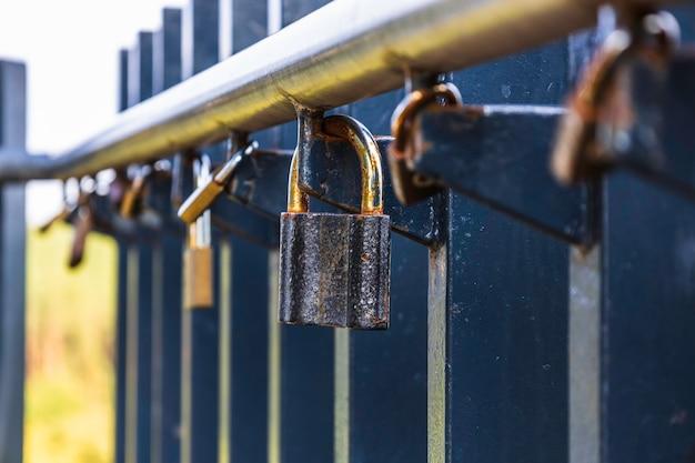 다른 사람들 사이에서 레일에 매달려 사랑 자물쇠 잡색의 자물쇠입니다.