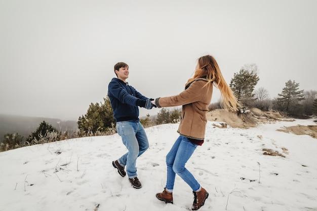 屋外の冬の降雪を受け入れる男女が大好きです。幸せな休日。メリークリスマスと新年あけましておめでとうございますのコンセプト。